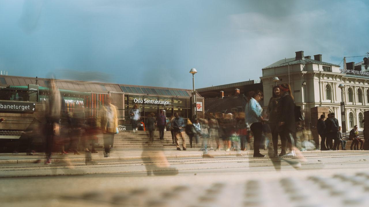 Oslo sentralstasjon med mennesker i bevegelse rundt.